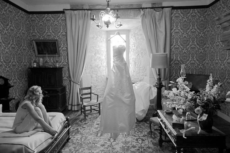 Mariée regarde sa robe suspendue