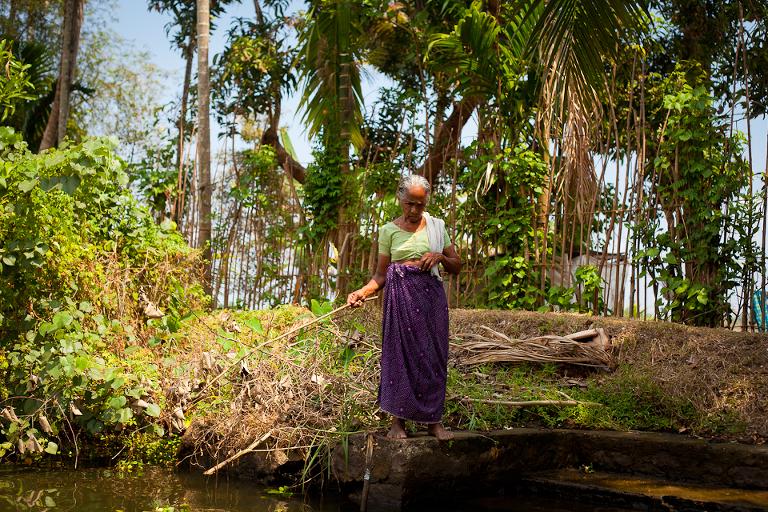Vieille dame pêchant avec une canne en bois dans les backwaters du Kerala