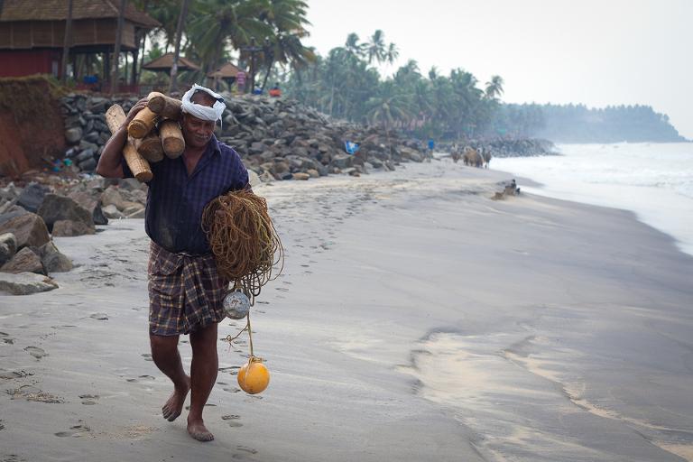 Pêcheur indien marchant sur la plage