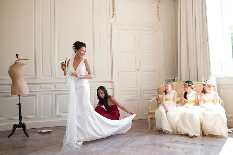 Mariée avec sa soeur qui l'aide à mettre sa robe