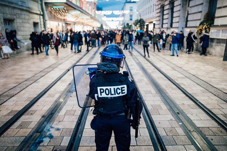 Policier devant une foule de manifestants